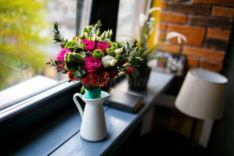 白色瓶子在木窗台的桃红色和白玫瑰 免版税库存照片