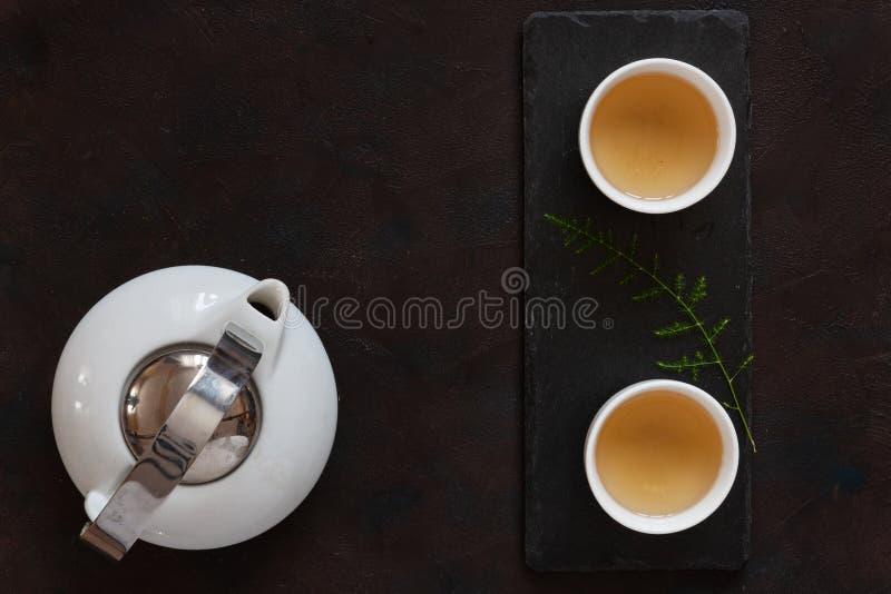 白色瓷亚洲茶具用在黑石书桌上的绿茶牛奶Oolong 关闭,顶视图 免版税库存图片