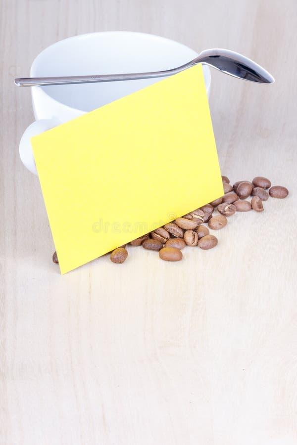 白色瓷咖啡杯特写镜头有匙子和愿望卡片的 库存照片