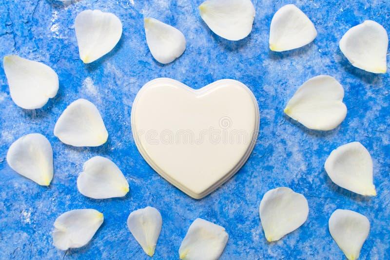 白色瓷心脏和玫瑰花瓣在天蓝色背景 r 免版税库存图片