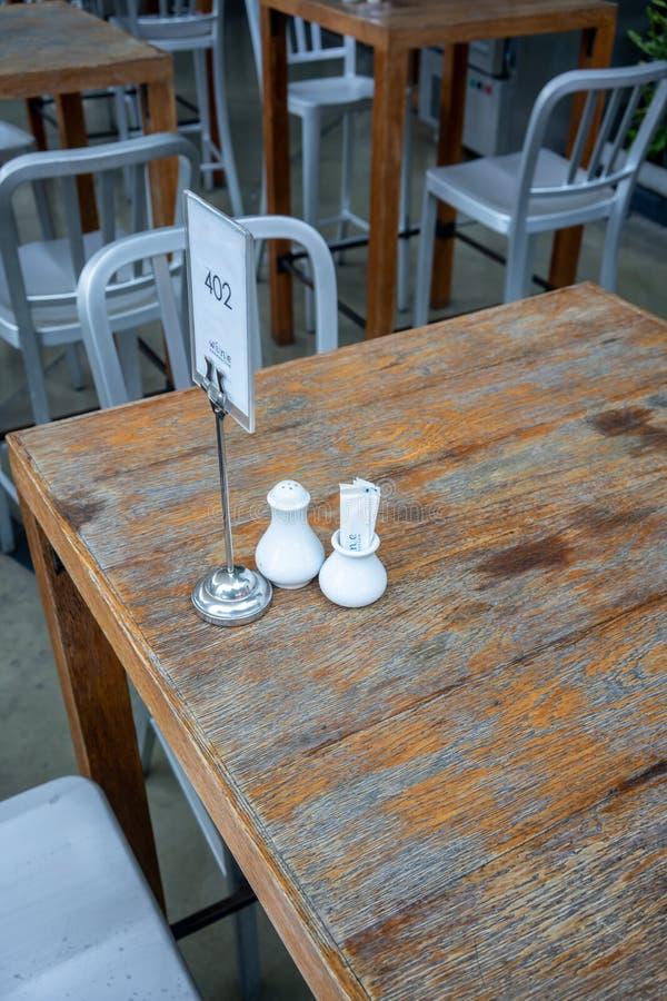 白色瓷胡椒振动器和牙签容器由桌 免版税图库摄影