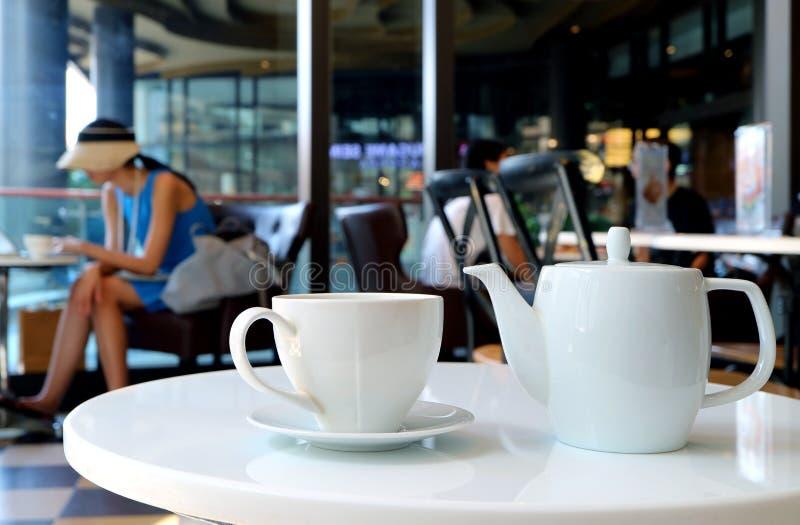 白色瓷茶具在咖啡馆的圆桌上服务 库存图片