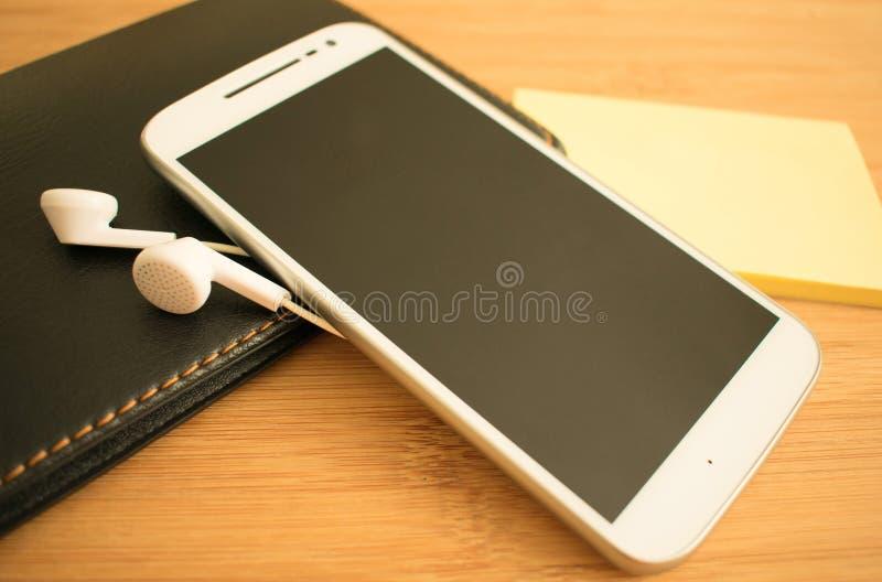 白色电话和耳机在桌上 库存图片