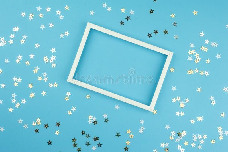 白色画框和衣服饰物之小金属片星在蓝色背景 库存照片