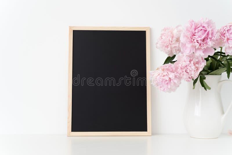 白色画象框架嘲笑与在框架旁边的桃红色牡丹,躺在了您的行情、促进、标题或者设计,伟大为s 免版税库存图片