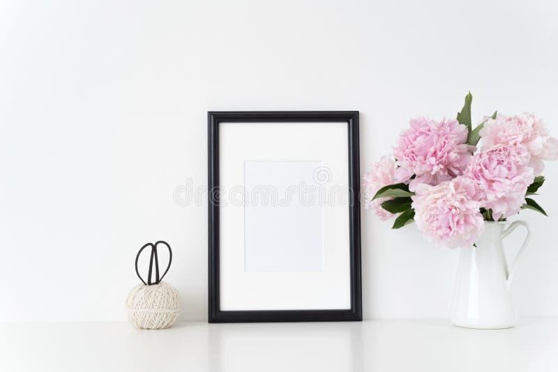 白色画象框架嘲笑与在框架旁边的桃红色牡丹,躺在了您的行情、促进、标题或者设计 库存图片