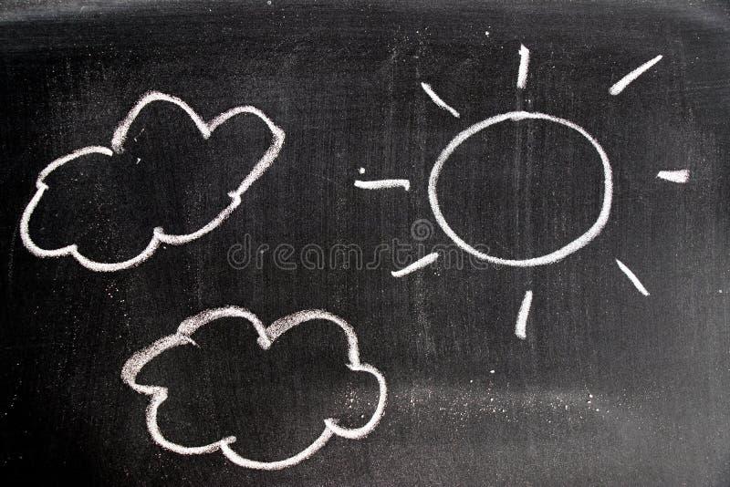 白色白垩手图画在太阳和云彩形状的在黑委员会背景 库存例证