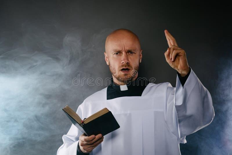 白色白色法衣的天主教教士和有教士衣领读书圣经的黑衬衣 免版税库存照片