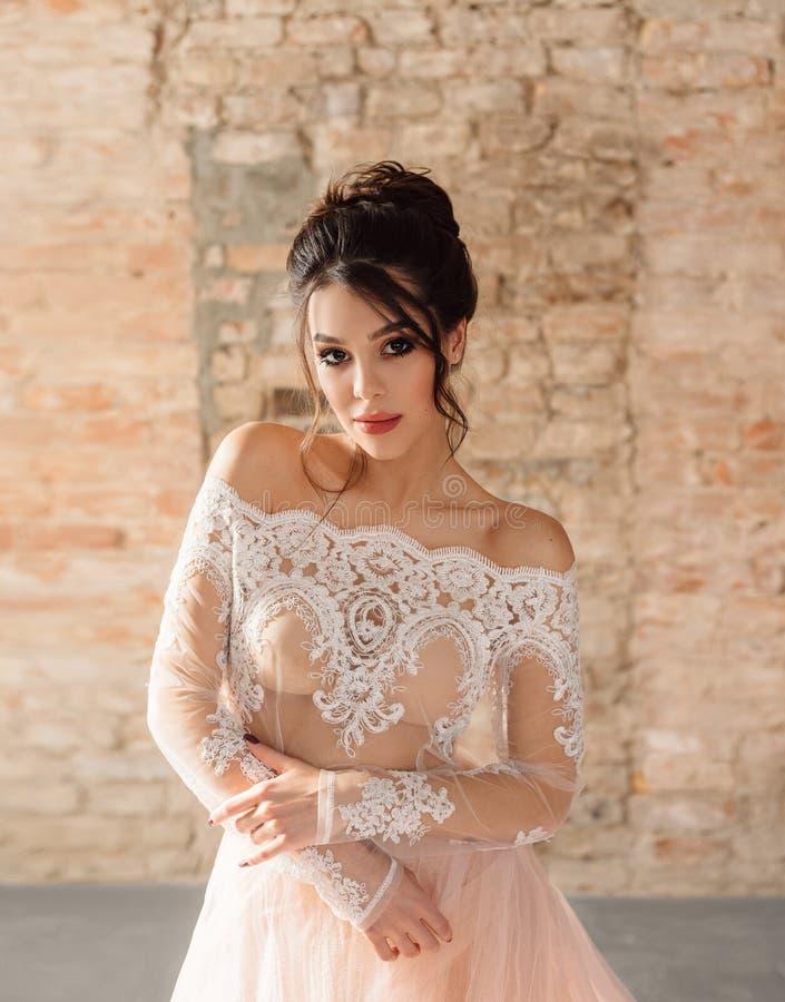 白色的一个年轻深色的女孩,与桃子裙子的鞋带上面 有红砖的背景墙壁 高发型,明亮 库存照片