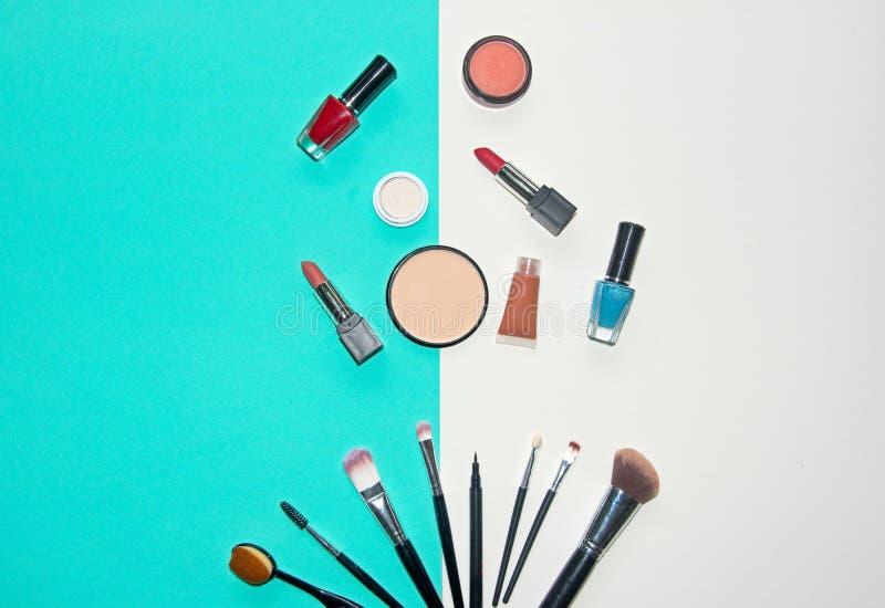 白色的化妆用品和蓝色背景与组成艺术家对象:唇膏,眼影,染睫毛油,眼线膏, concealer,指甲油 图库摄影
