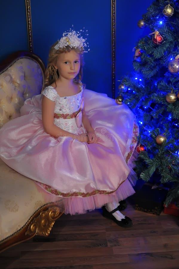 白色的女孩与在圣诞节的一件桃红色礼服 免版税库存照片