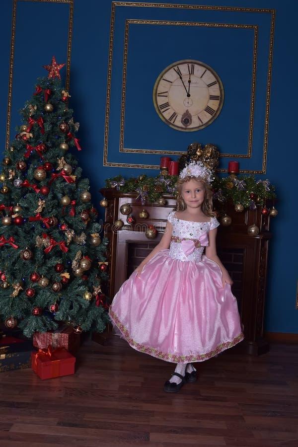 白色的女孩与在圣诞节的一件桃红色礼服 图库摄影