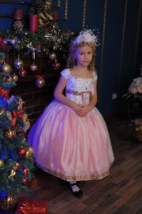 白色的女孩与在圣诞节的一件桃红色礼服 库存照片