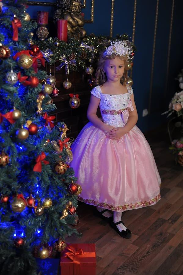 白色的女孩与在圣诞节的一件桃红色礼服 免版税库存图片