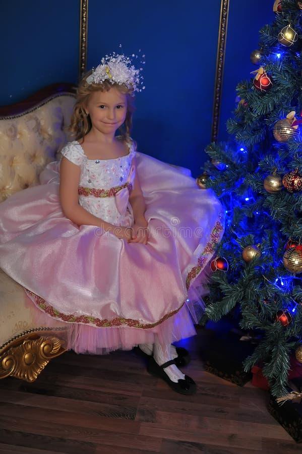 白色的女孩与在圣诞节的一件桃红色礼服 免版税图库摄影