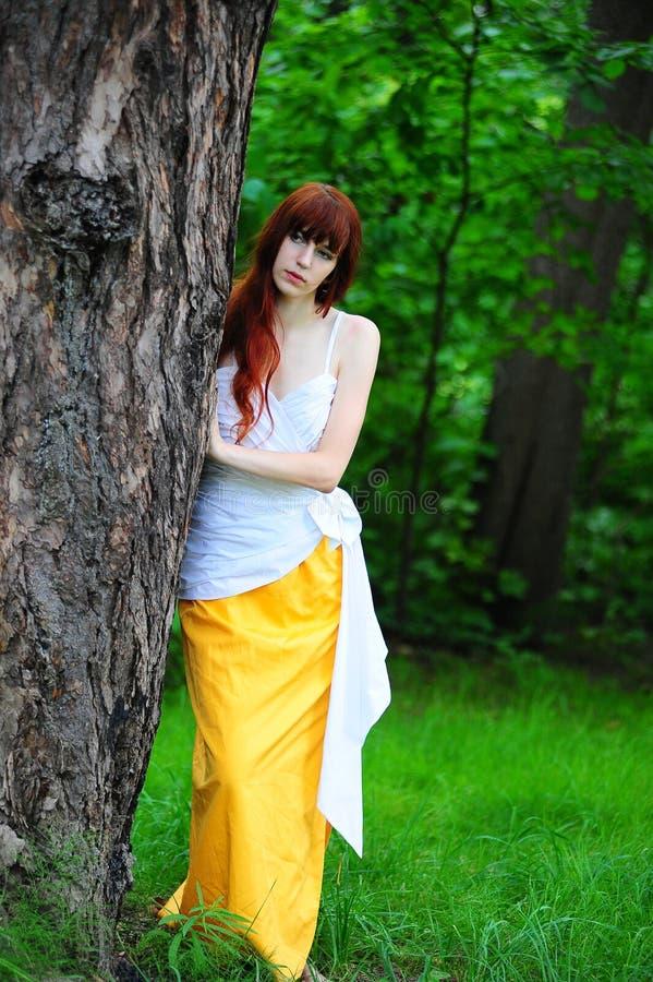 白色的女孩与由树的一件黄色晚礼服 图库摄影