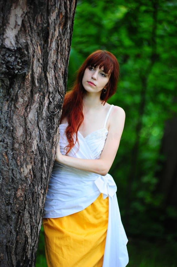 白色的女孩与由树的一件黄色晚礼服 库存图片