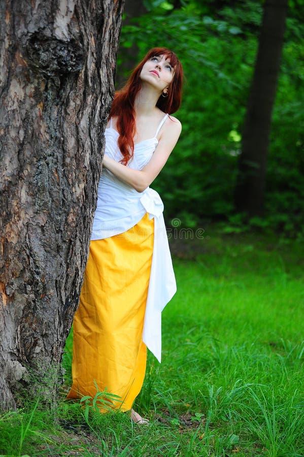 白色的女孩与由树的一件黄色晚礼服 免版税库存照片