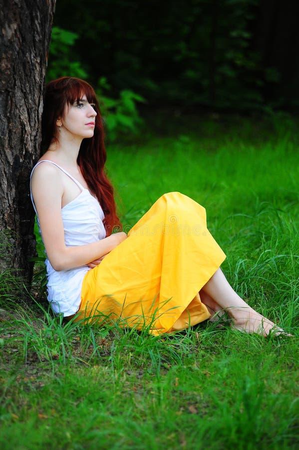 白色的女孩与由树的一件黄色晚礼服 免版税库存图片