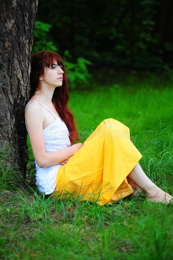 白色的女孩与由树的一件黄色晚礼服 库存照片