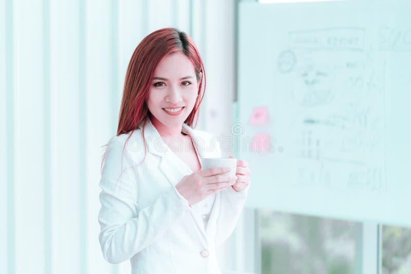 白色的年轻女人休假用热的咖啡 库存图片