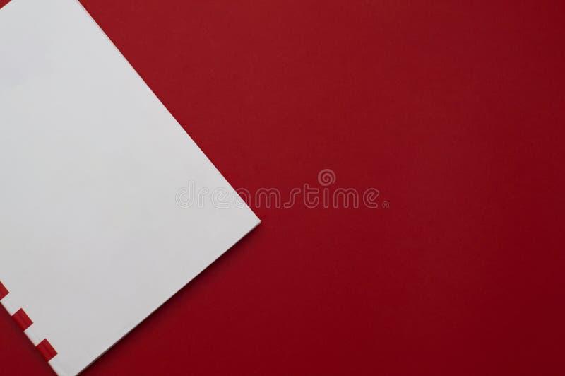白色的正面图与红色的镶边在简单的红色背景的便笺零件 库存照片
