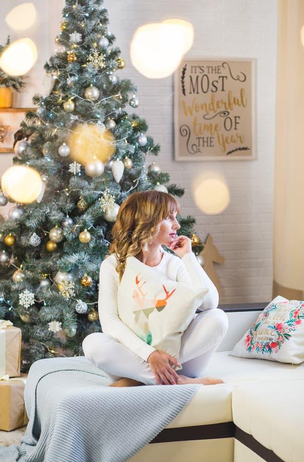 白色的美丽的年轻女人与大圣诞礼物 库存图片
