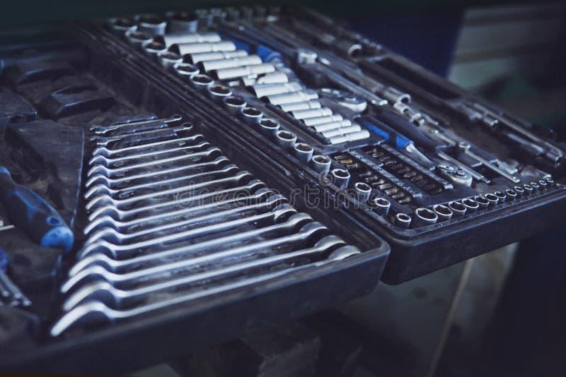 白色的背景配件箱关闭查出的工具 成套工具以保留板钳的内部隔间,圆环扳手,锤子,钳子,螺丝刀,活动扳手,螺丝 免版税库存图片