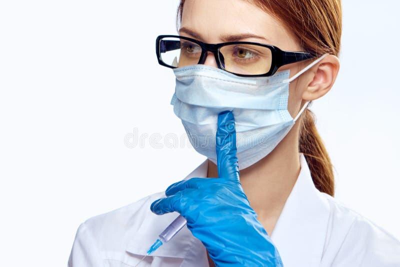 白色的年轻美丽的妇女隔绝了与玻璃和医疗面具,医学医生的,背景 库存照片