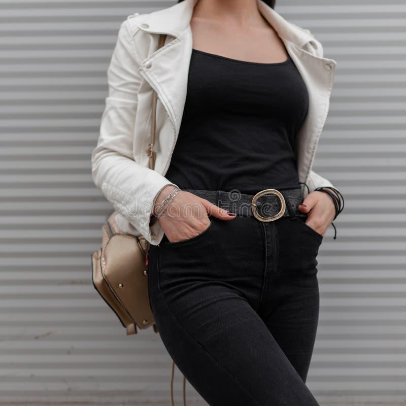 白色皮夹克的年轻女人在黑牛仔裤的一件T恤杉有一个时髦的金黄背包的在现代墙壁附近摆在 E 库存照片