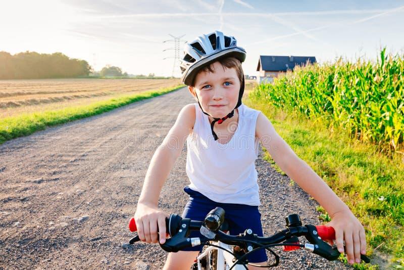 白色盔甲的愉快的小孩男孩在自行车 库存图片