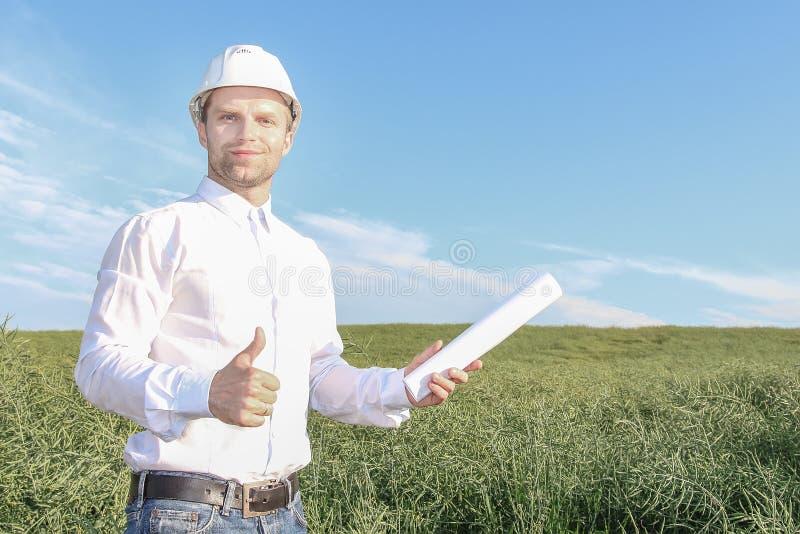 白色盔甲的愉快的工程师建筑师与举行他赞许和微笑的图纸 免版税库存照片