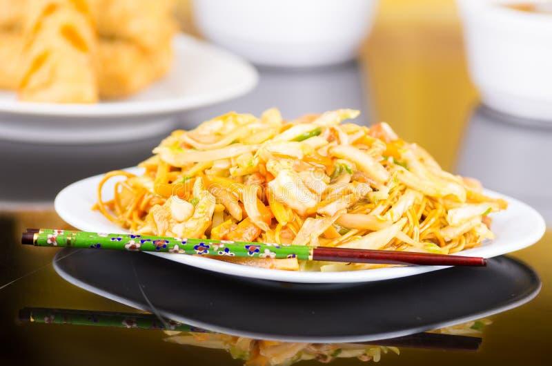 白色盘用中国食物、面条和菜 在边的筷子 图库摄影