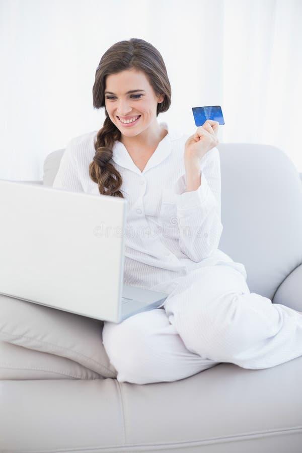 白色睡衣的笑的偶然棕色毛发的妇女在网上购物与她的膝上型计算机的 免版税库存图片