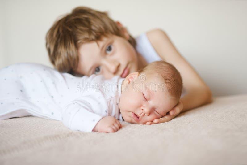 白色睡衣的婴孩睡觉在他的胃的,更老的兄弟拥抱 库存图片