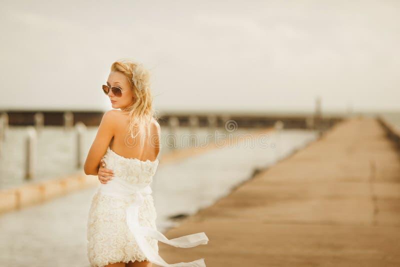 白色短的婚礼礼服的妇女 玻璃的新娘与站立在码头的金发 免版税库存照片