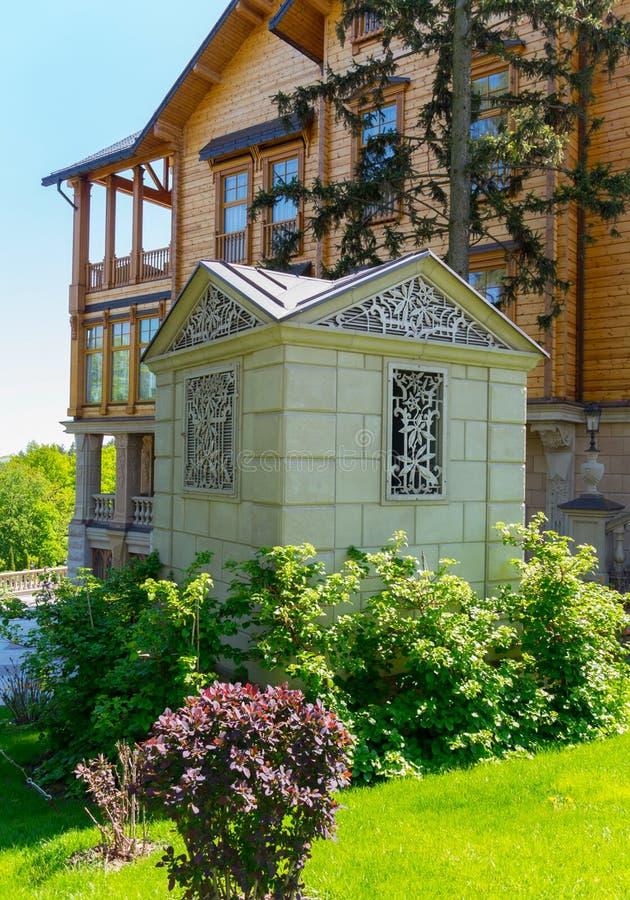 白色石头一个小装饰大厦在一个巨大的木豪宅前面的在明亮的水多的绿色背景和 库存图片