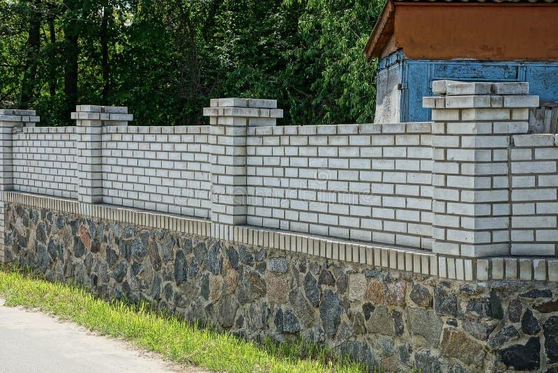 白色砖和灰色石头长的私有篱芭  免版税图库摄影