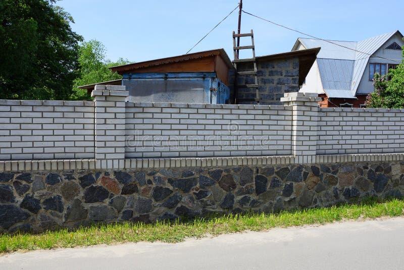 白色砖和灰色石头长的私有篱芭  免版税库存图片