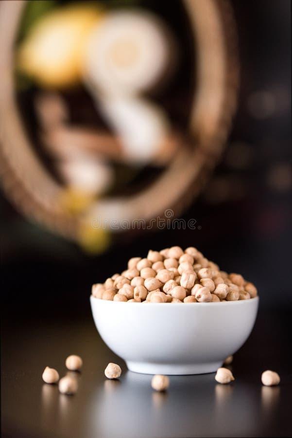 白色碗在木桌上的未加工的鸡豆 免版税库存照片