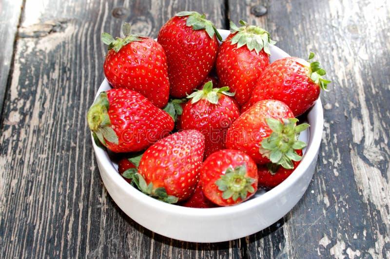 白色碗在木桌上的红色草莓 库存照片