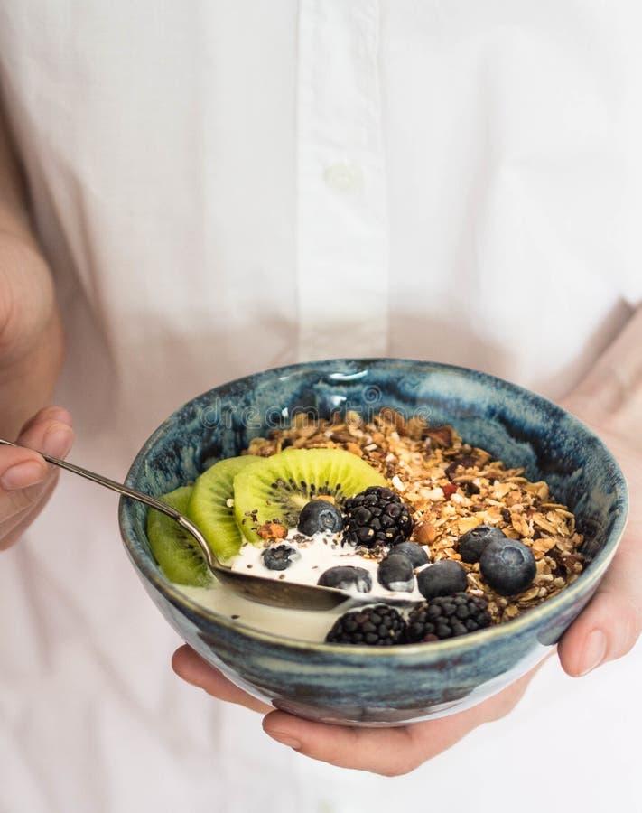白色碗自创格兰诺拉麦片,酸奶,在木委员会的新鲜的莓果 素食食物,健康早餐 免版税库存图片