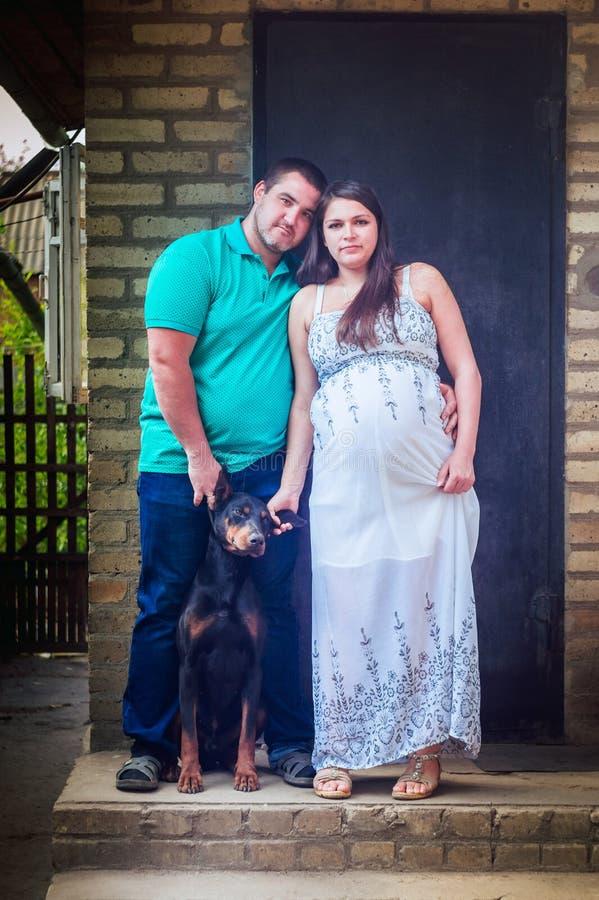 白色礼服、她的丈夫和短毛猎犬的孕妇 免版税图库摄影