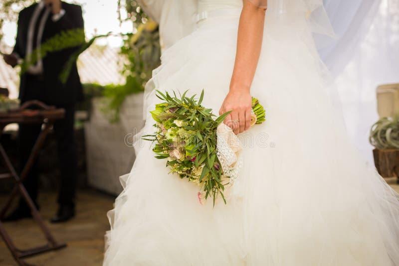 白色礼服举行婚礼boquet的新娘在她的手上 库存图片
