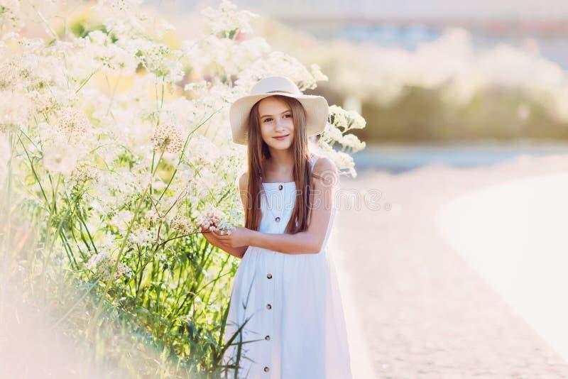 白色礼服和帽子的好女孩走在大花附近的 免版税图库摄影