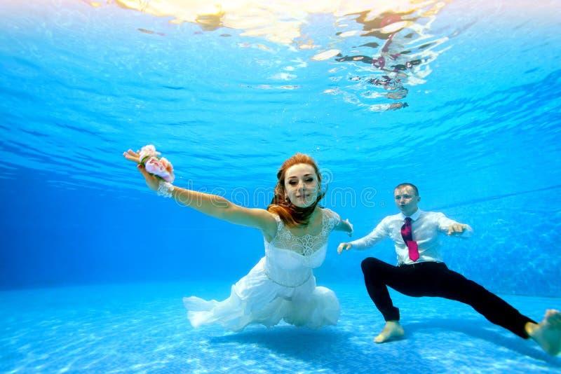 白色礼服和新郎游泳的新娘和摆在水面下在照相机在水池的底部在清楚的大海 ?? 免版税库存图片