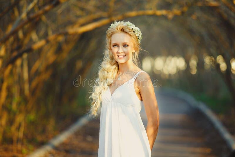 白色礼服和花卉花圈的美丽的白肤金发的妇女在她的头 胡同的逗人喜爱的人 免版税图库摄影
