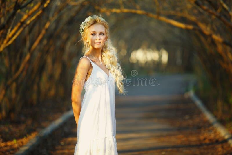 白色礼服和花卉花圈的美丽的白肤金发的妇女在她的头 胡同的逗人喜爱的人 库存照片