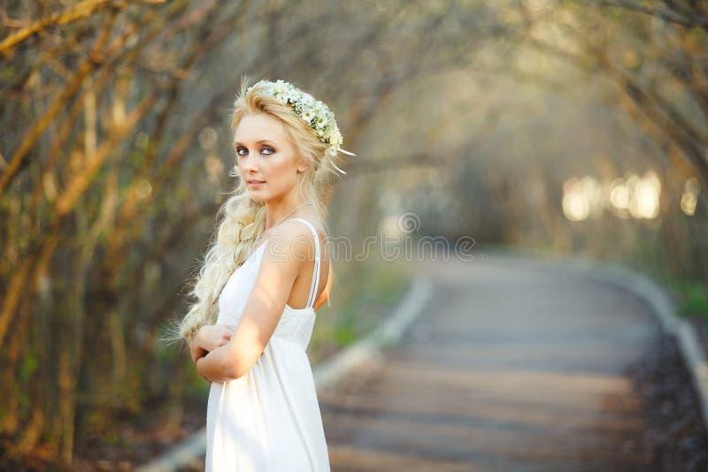 白色礼服和花卉花圈的美丽的白肤金发的妇女在她的头 胡同的逗人喜爱的人 免版税库存图片