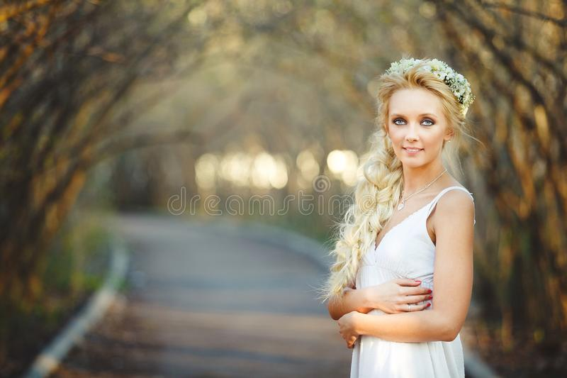 白色礼服和花卉花圈的美丽的白肤金发的妇女在她的头 胡同的逗人喜爱的人 库存图片